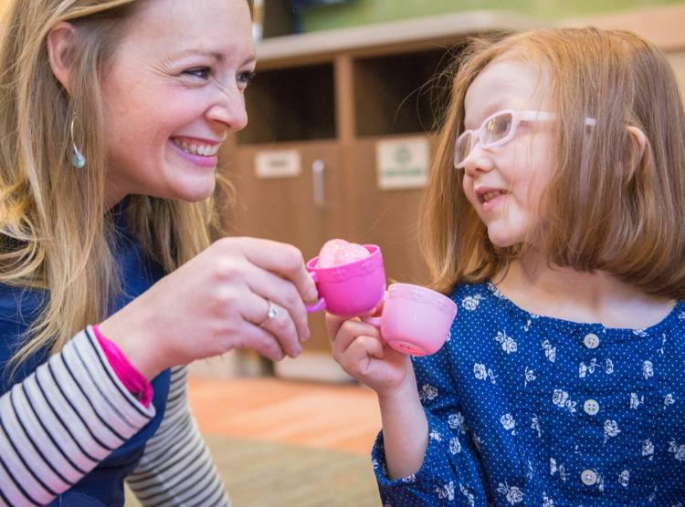 Gillette patient Ashlyn and nurse playing tea at Gillette children's specialty healthcare