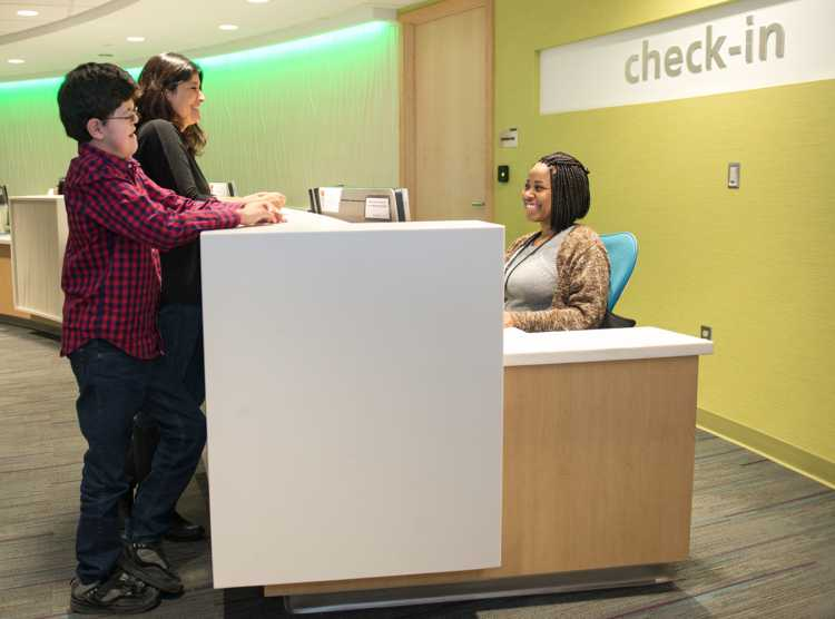 Gillette patient Michael checking in at reception desk with his mom.