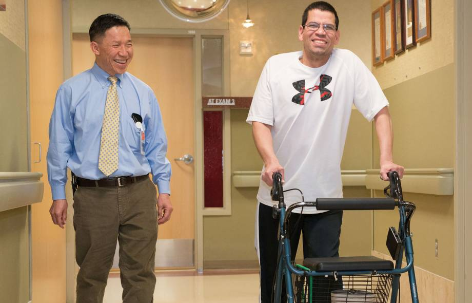 Lee Schuh, MD, walks down hallway with patient at Gillette children's specialty healthcare