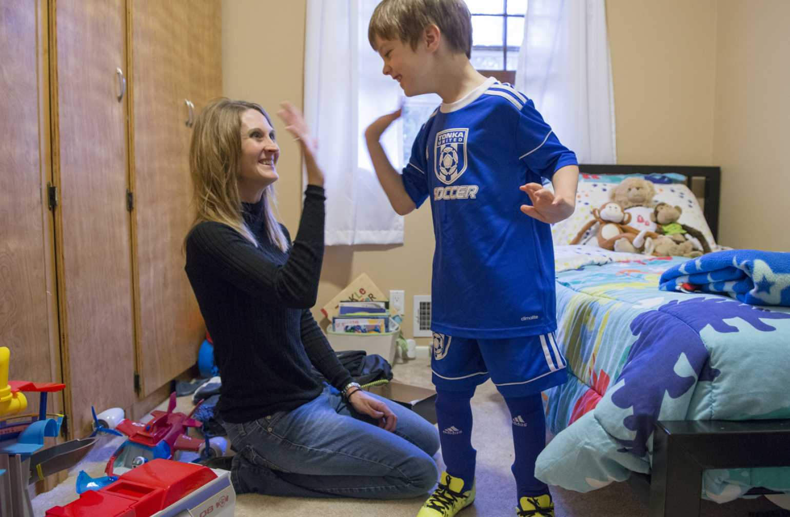 gillette patient ezra at home with mom giving a high five