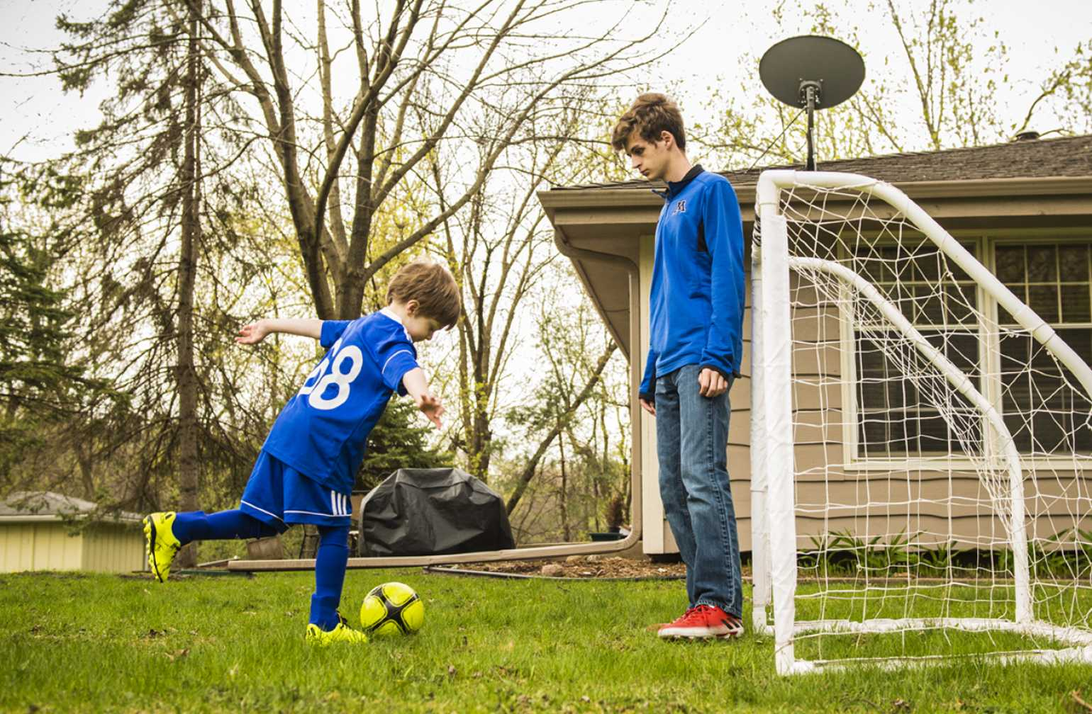 gillette patient ezra runs and practices kicking a goal at home