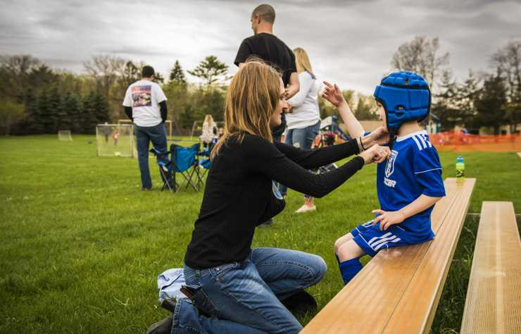 Gillette patient Ezra with mom on soccer field during game