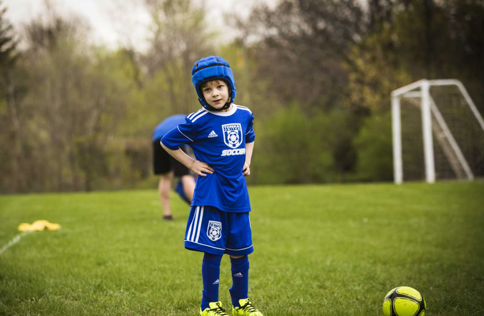 Gillette patient, Ezra, standing alone on field with soccer ball and goal
