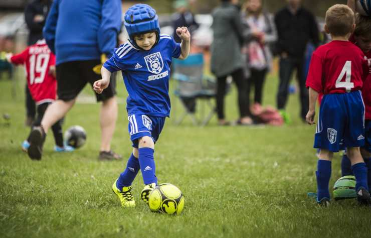 Gillette patient Ezra runs to kick soccer ball during game