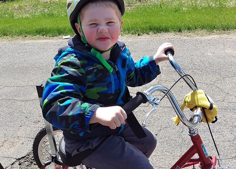 Five year old Gillette patient Gavin rides his adaptive bike