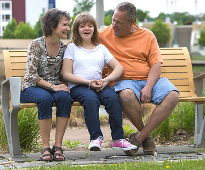Jill sitting on a bench with her mom and dad