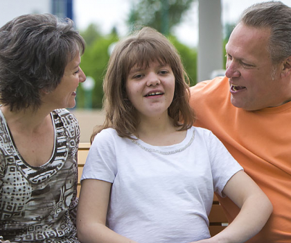 close up shot of Jill sitting on park bench with mom and dad