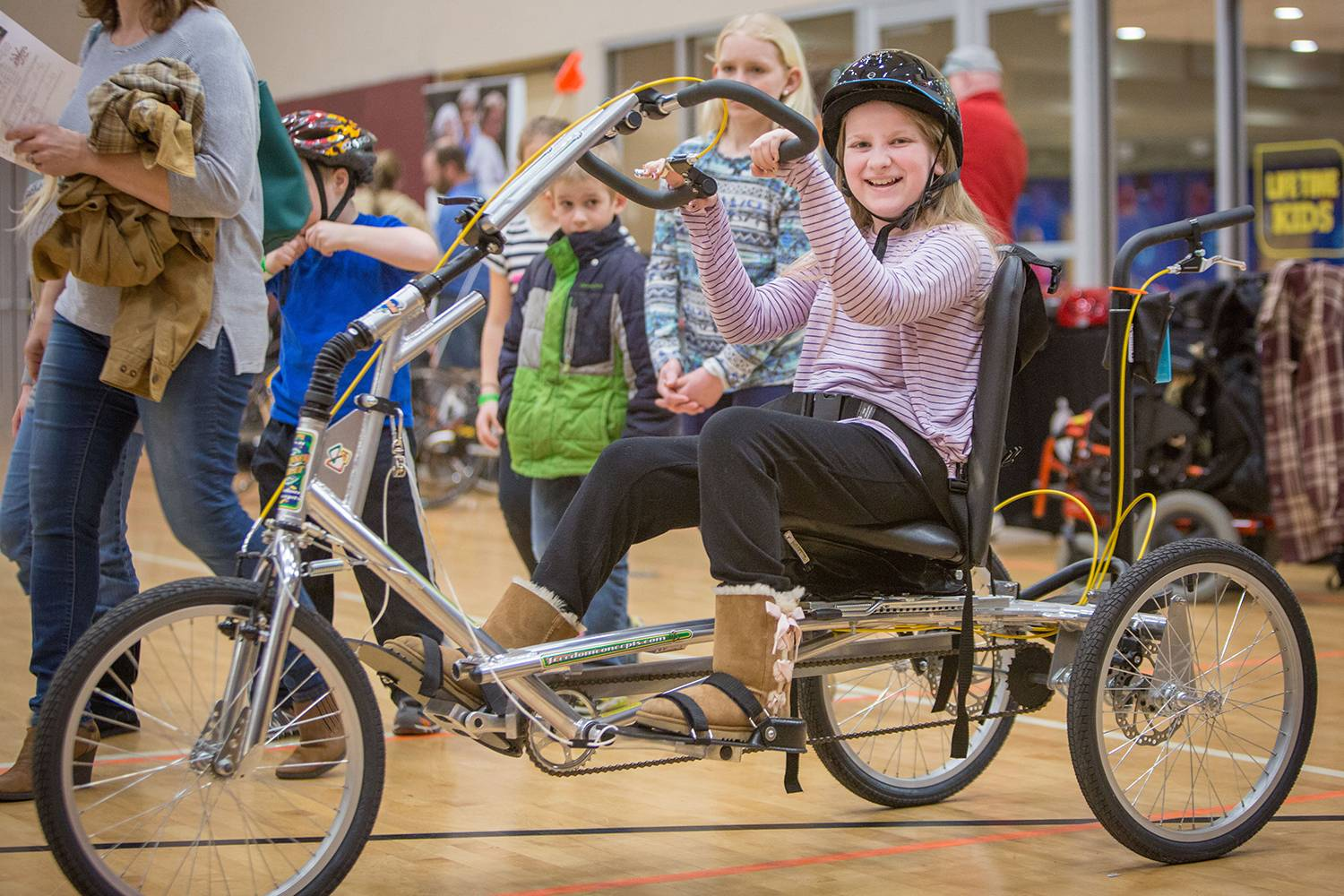 Kiara tries her first adapted bike at the expo.