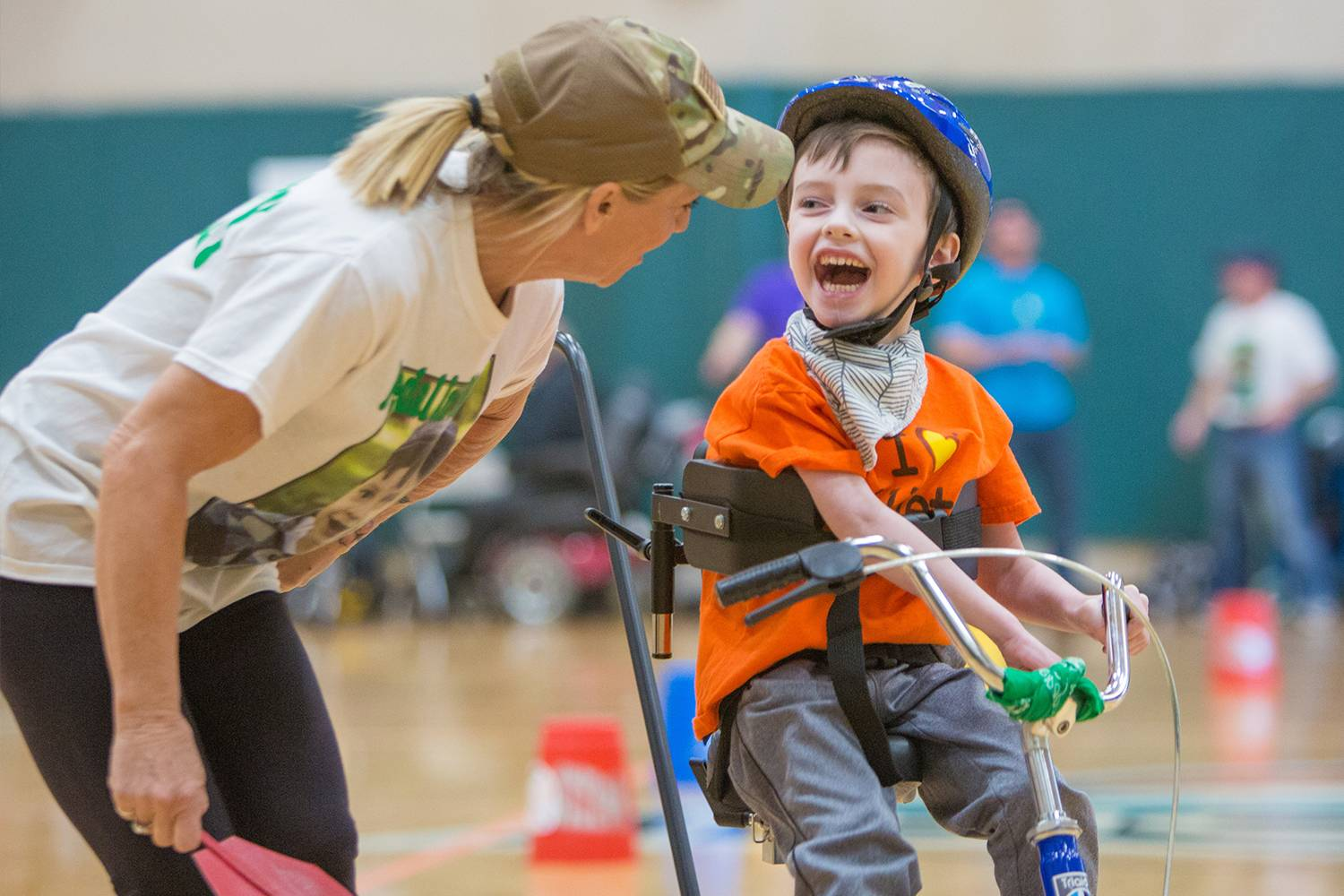 A boy smiles as he tries an adapted bike at the expo.