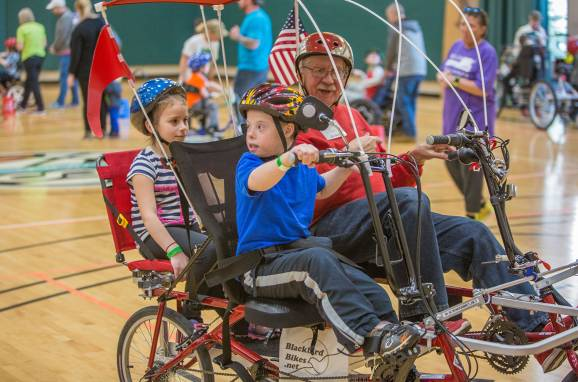 Three children try an adaptive bike