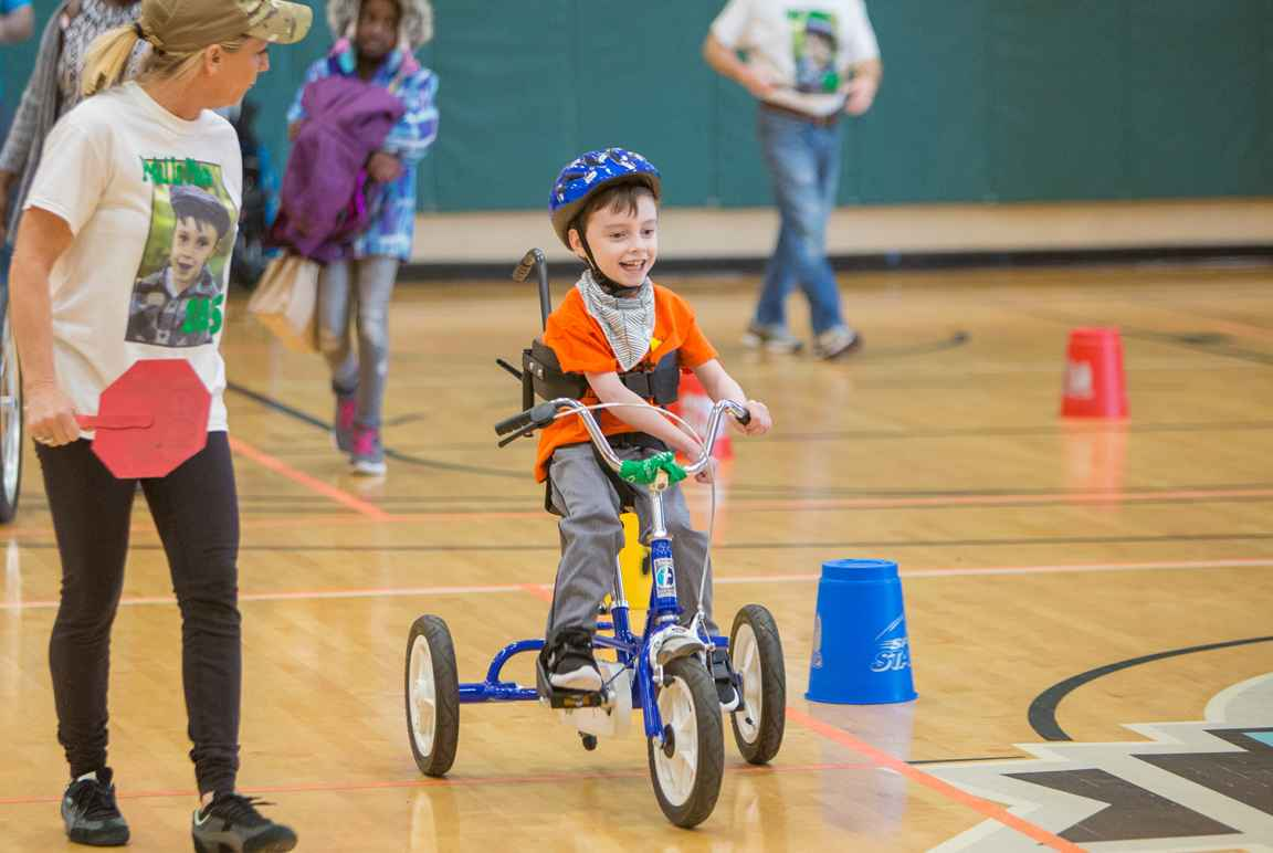 One child rides adaptive bike with therapist