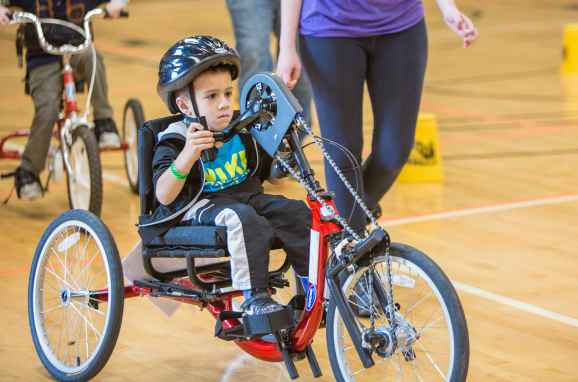 Boy tries out a red adaptive bike during Gillette bike expo