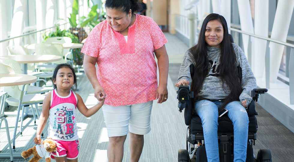 Gillette Children's spinal cord injury patient Guadalupe with her family in skyway