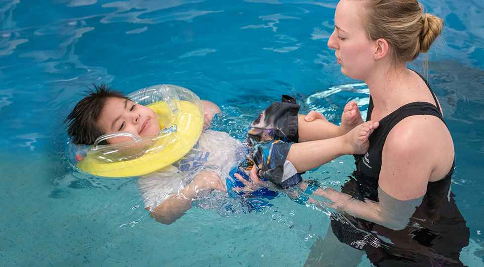 Physical therapist during aquatic pool therapy with Gillette patient.