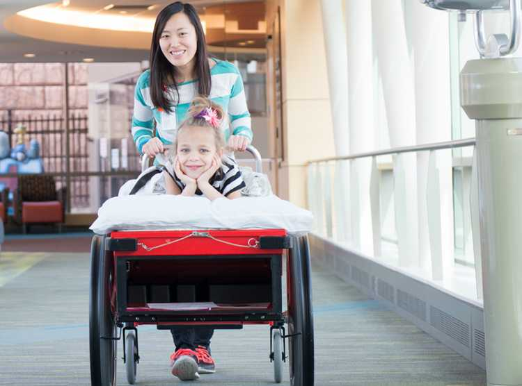 Volunteer with patient Patience helping with prone cart at Gillette children's
