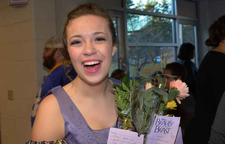 Gillette patient Eliza holding flowers after her performance