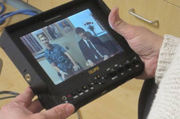 A teacher holds a broadcasting monitor.