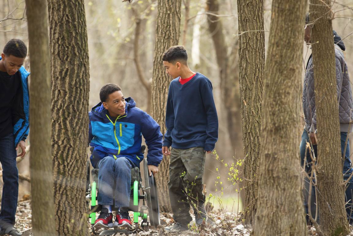 Elijah pushes his wheelchair through the woods with brother and friend
