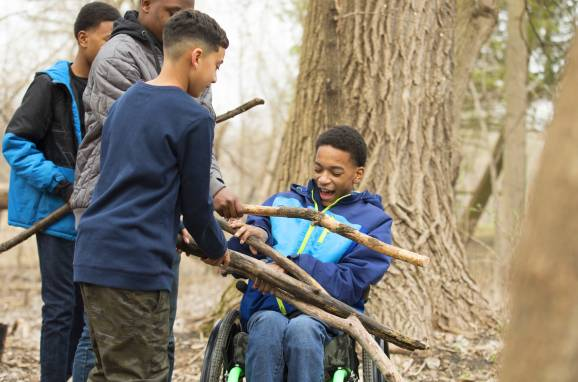 Elijah helps gather fire wood with brother and friends