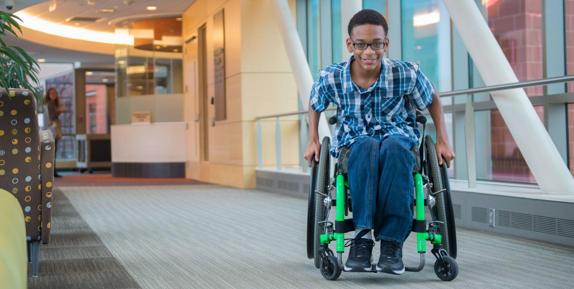 Gillette patient Elijah using wheelchair near rehab therapies in skyway.