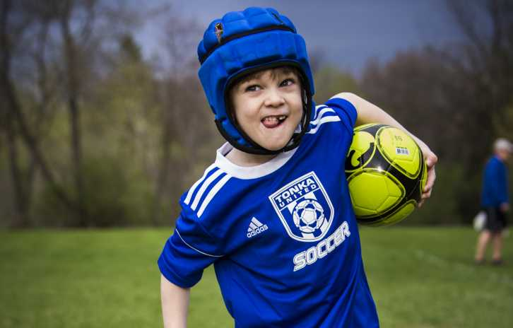 Gillette children's patient Ezra enjoys running on the soccer field holding ball