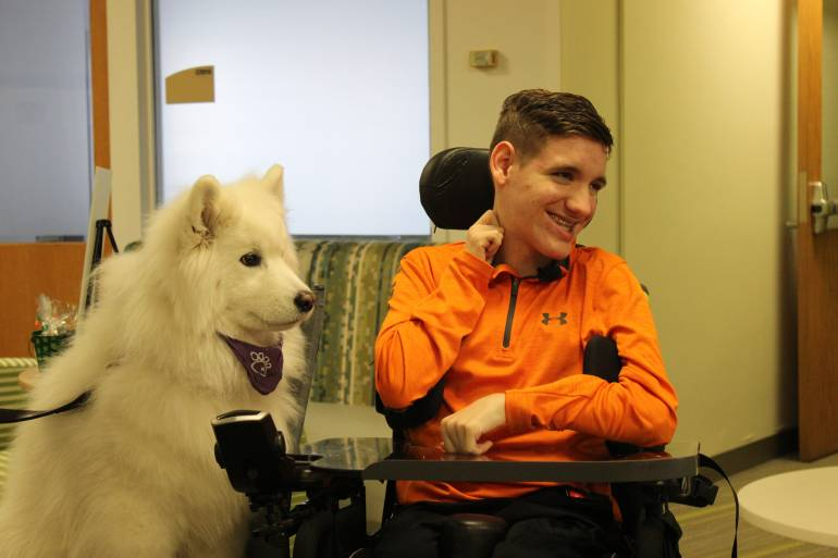 Gillette patient Nick, smiling with Gillette therapy dog, Sara