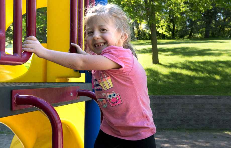Gillette patient Hope plays on playground equipment outdoors.