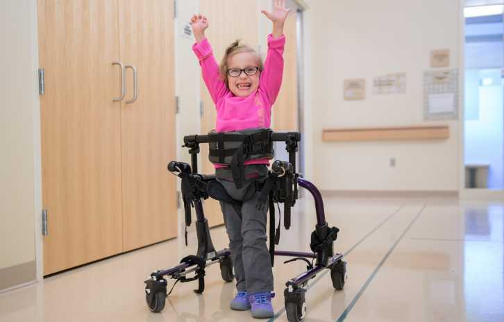 Gillette CP patient, Kaidyn stands with her walker at Gillette