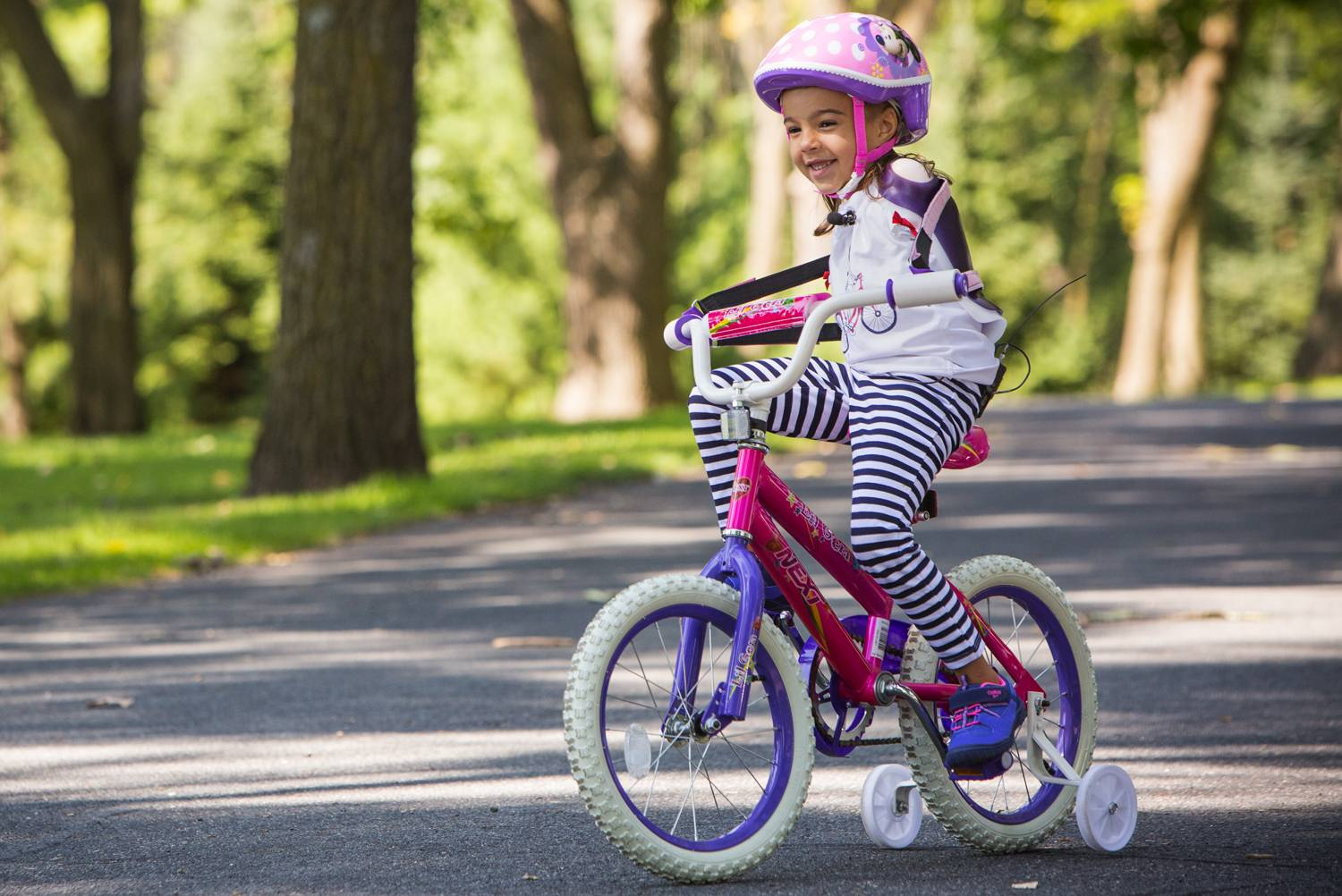 Gillette patient Ruth Evelyn (RE) who was born without arms rides her bike