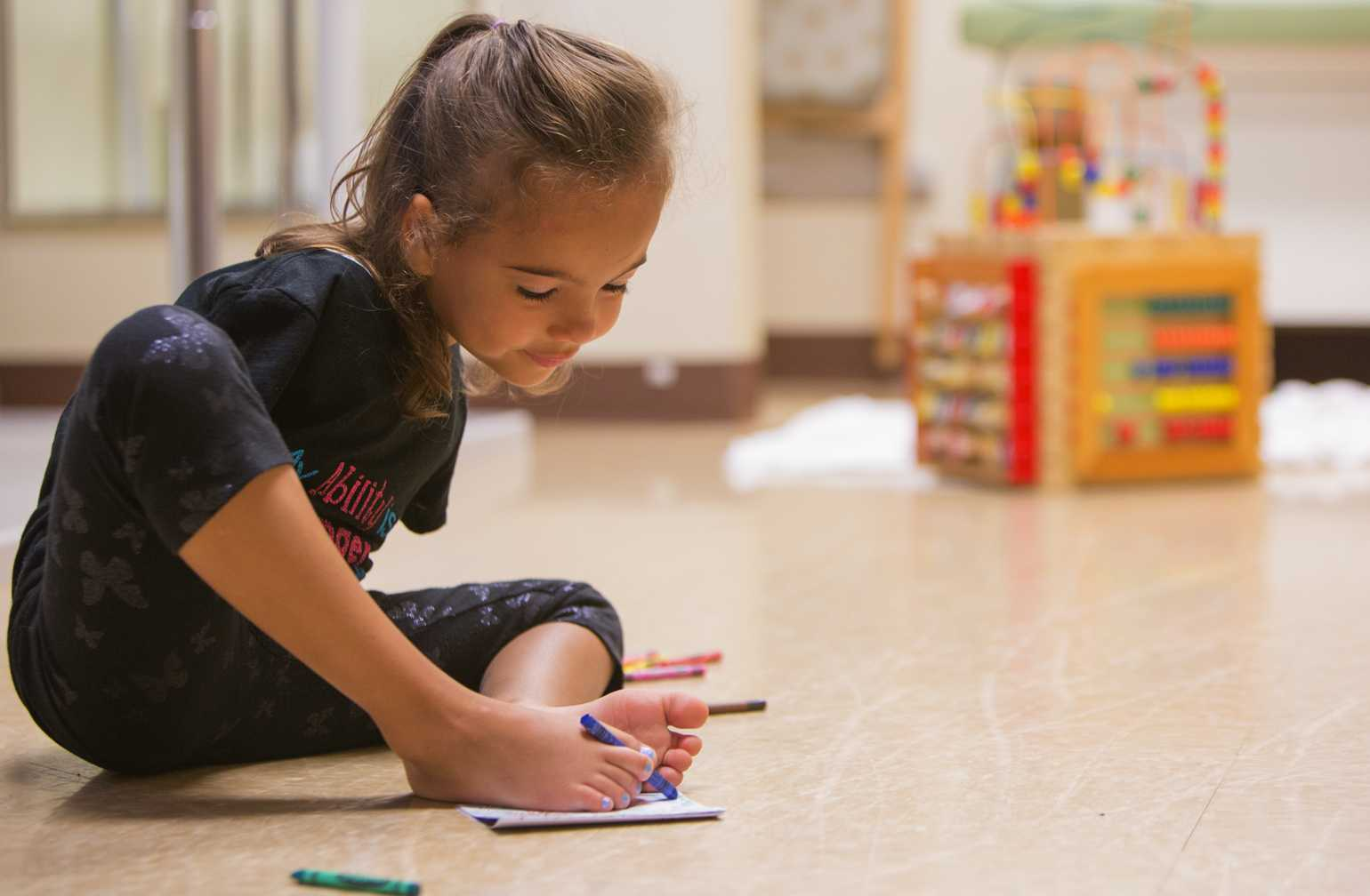 Gillette Children's patient Ruth Evelyn, born without arms colors on the floor
