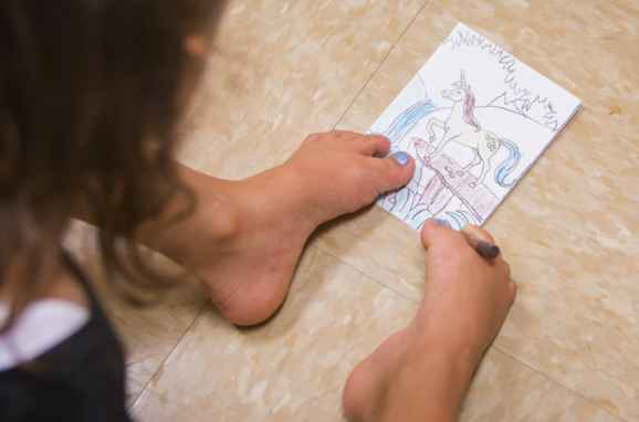 A close up of Gillette Children's patient Ruth Evelyn's feet as she uses them to color instead of arms.