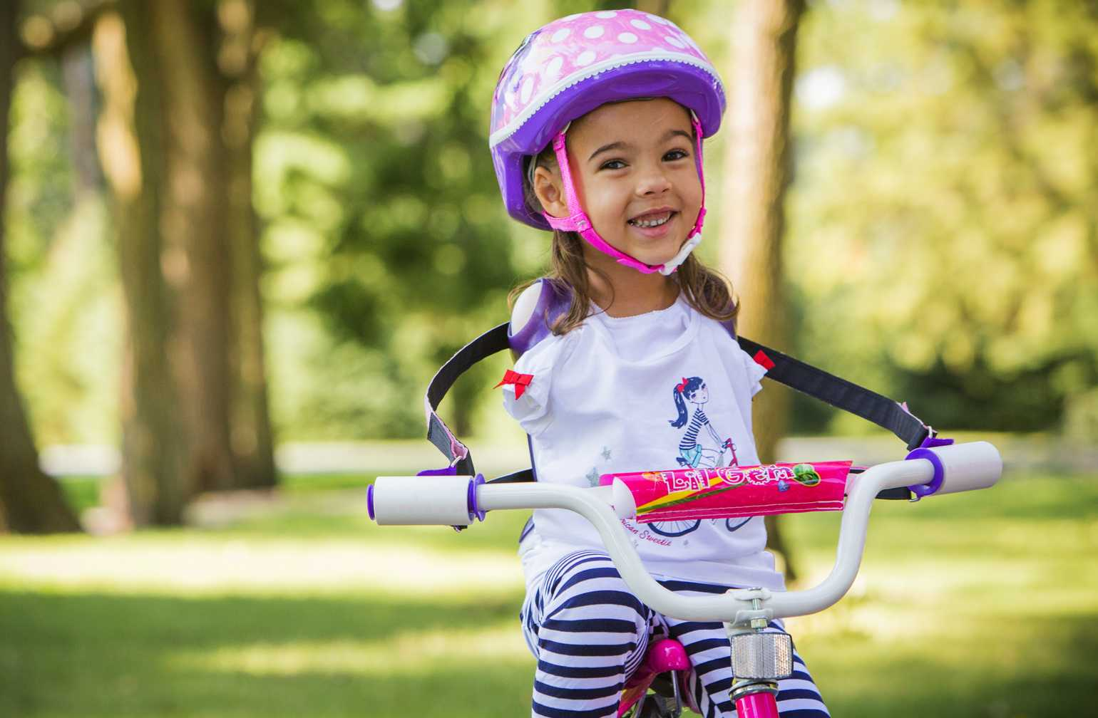 Ruth Evelyn, Gillette Children's patient who was born without arms poses with her bike