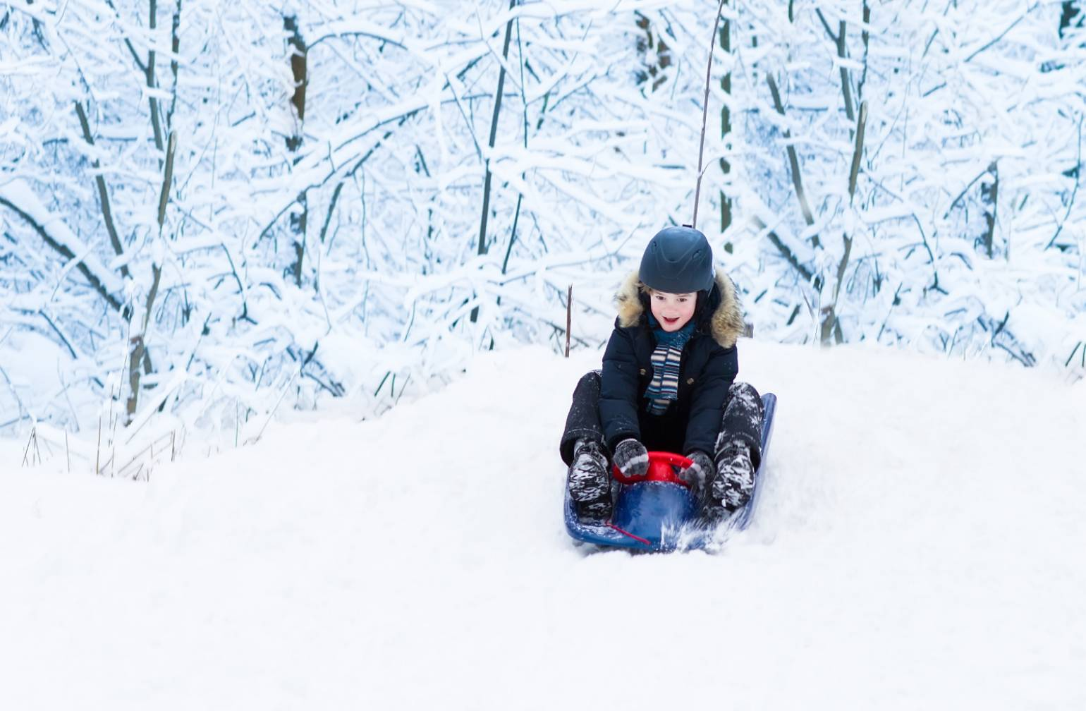 Boy sledding in the snow during winter.