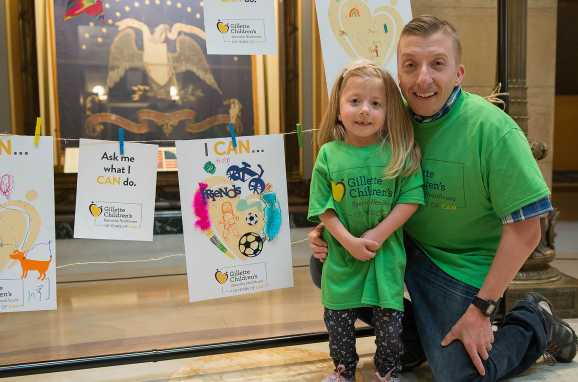 Gillette patient poses with her dad near artwork during capitol day