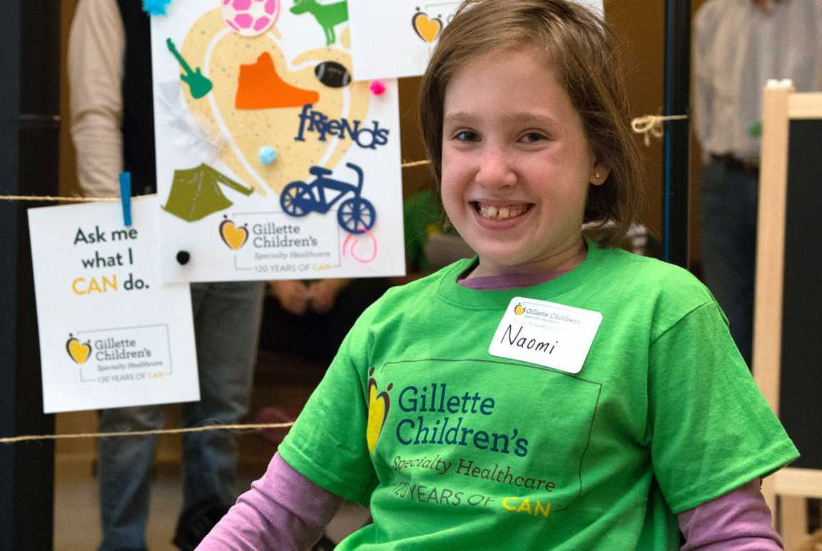 Gillette patient smiles while posing near artwork for capitol day