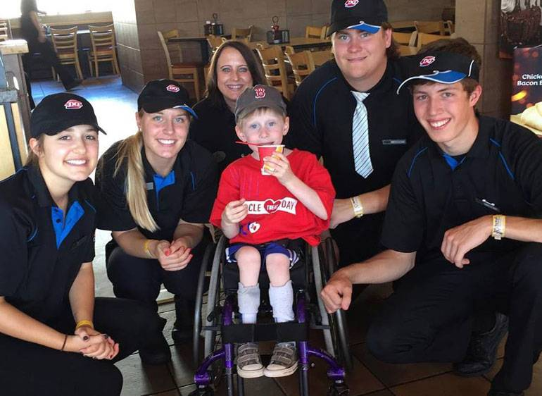 Dairy Queen workers gather around a Gillette Children's patient to enjoy a Blizzard.