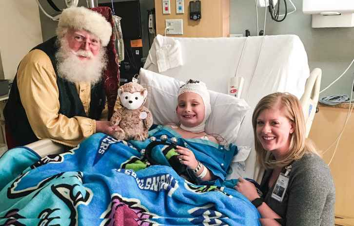Santa Carlucci and Jamie Yuen bring some holiday cheer to Anthony as he recovers in the Gillette Pediatric Intensive Care Unit.