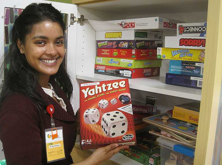 Gillette Children's volunteer holds game of Yahtzee