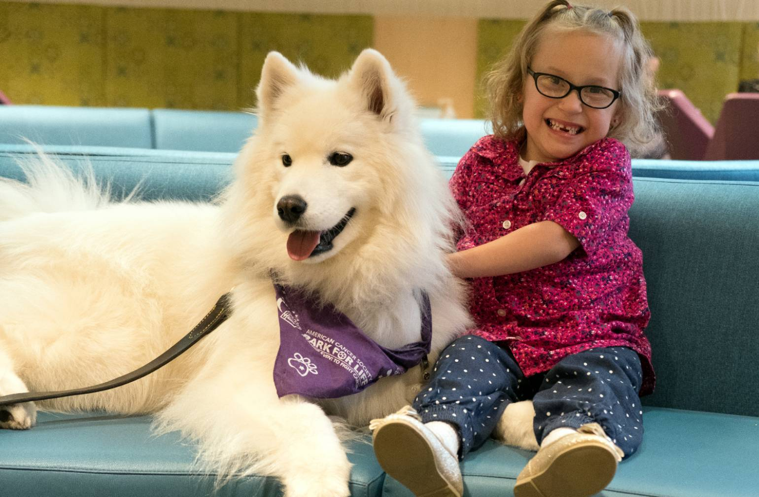 Gillette patient Kaidyn with therapy dog at Gillette.