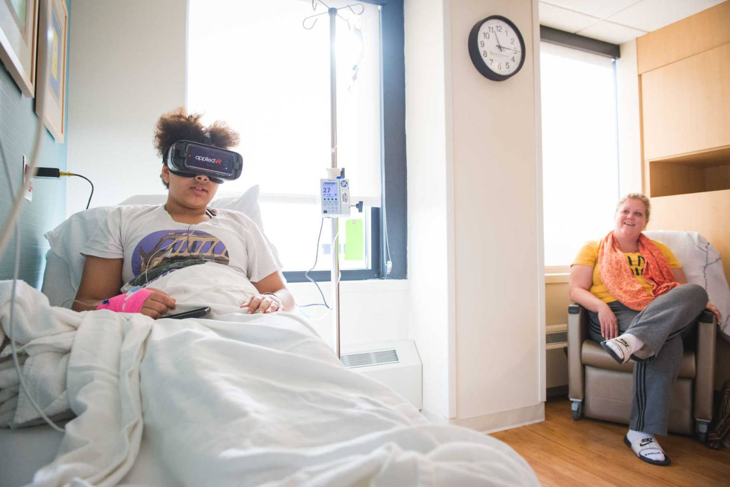 Olivia uses VR during her transfusion while her mother looks on