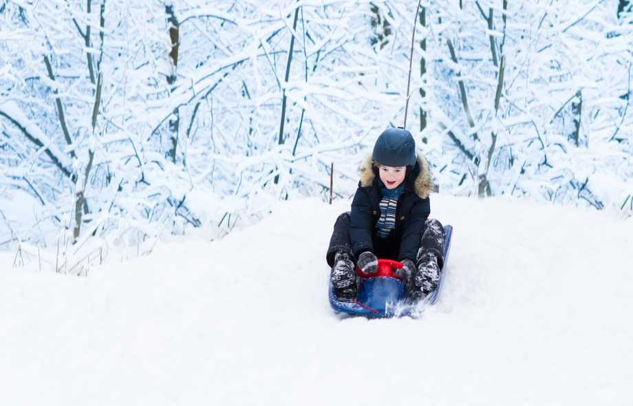 Image of child sledding and using a helmet