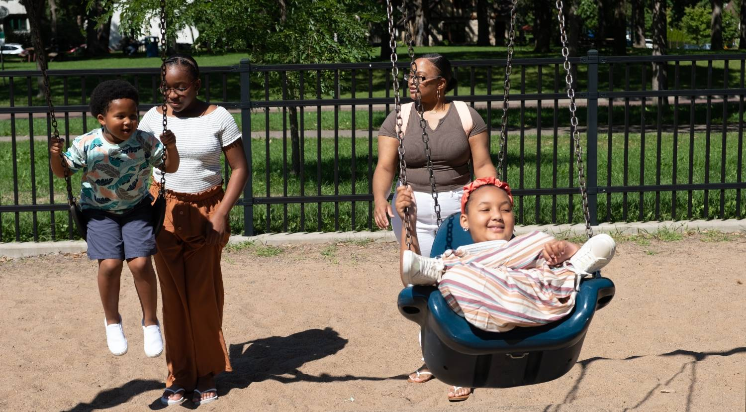 Za'Nii and her brother Amir on the swings at the park