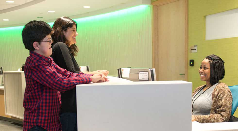 Gillette patient Michael Ruud and his mom checking in a front desk
