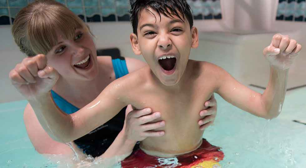 Gillette patient Masood in pool with physical therapist, fundraise for Gillette