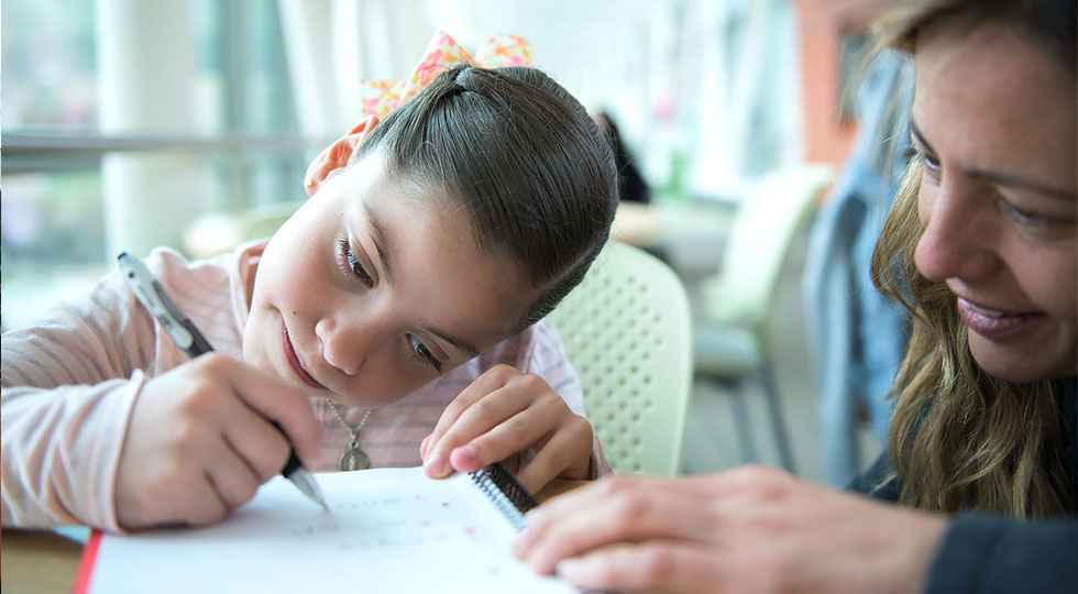 Gillette patient Maria renata writing with her mom, school services