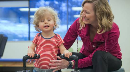 Lincoln with Kristine during physical therapy session at Gillette children's speciality healthcare minnetonka therapies location.
