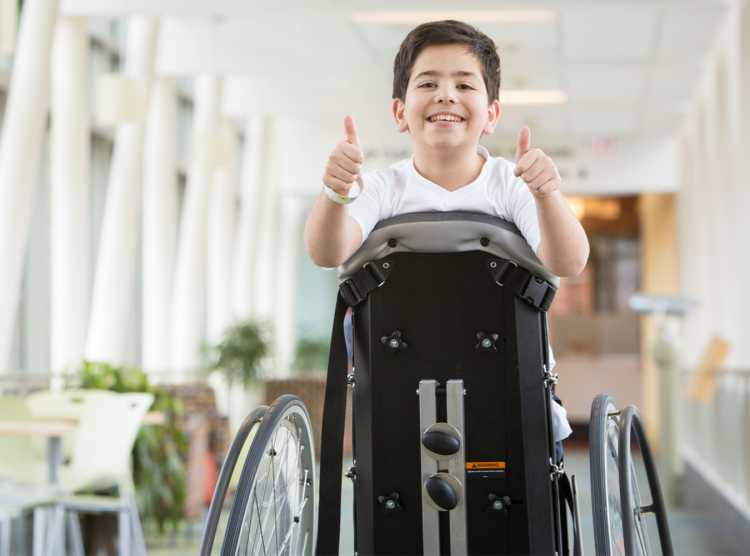 Gillette patient on stander giving two thumbs up in skyway