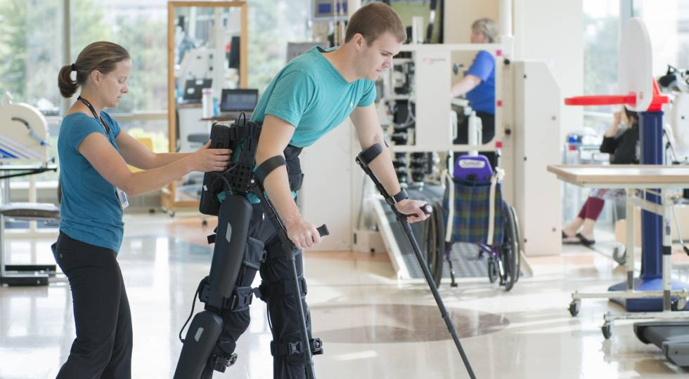 Gillette patient Jackson working with physical therapist and robotic exoskeleton