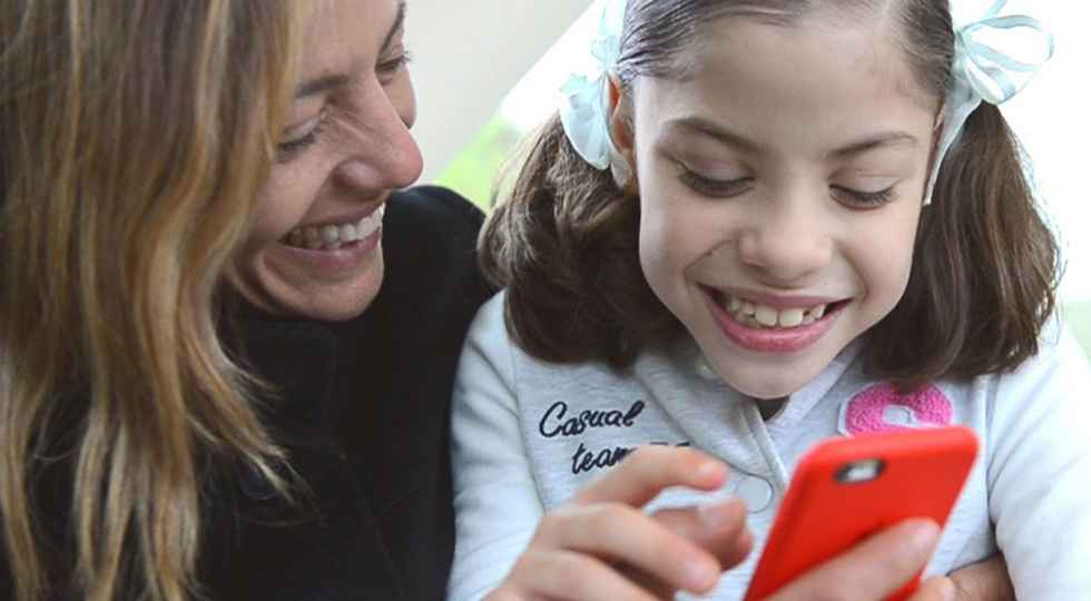 Gillette patient Maria using phone with mom.