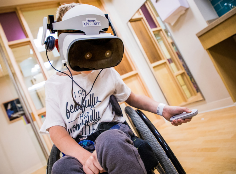 Patient in a wheelchair uses a VR headset donated through our partnership with the Starlight Foundation